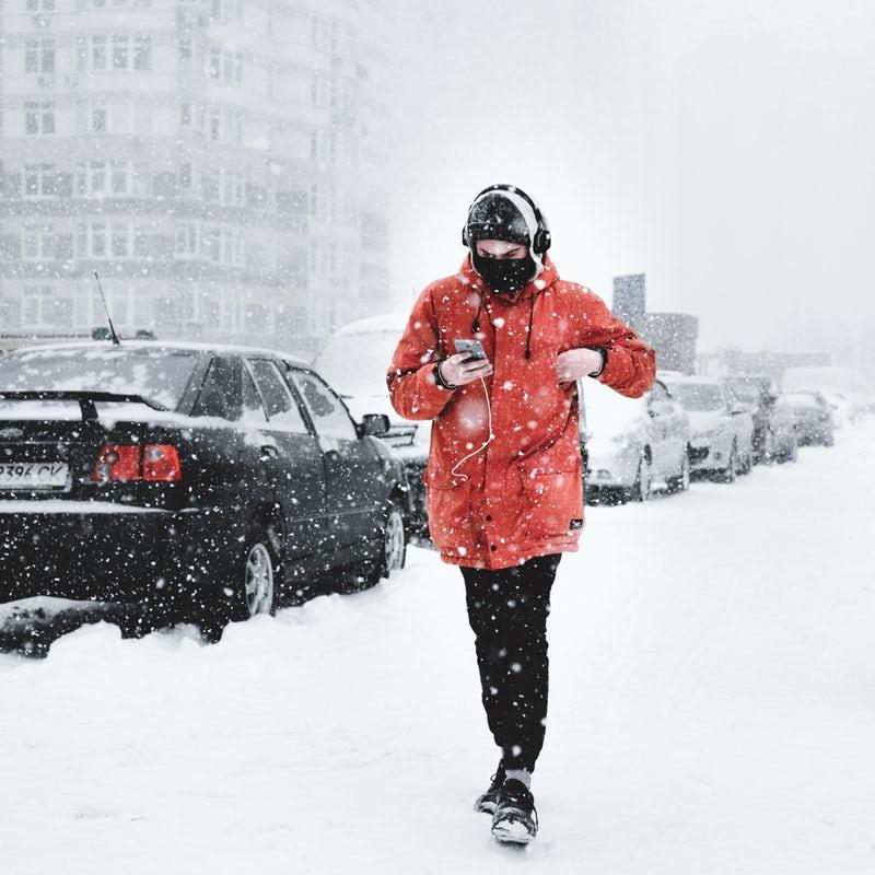 Ragazzo che cammina sotto la neve ascoltando musica