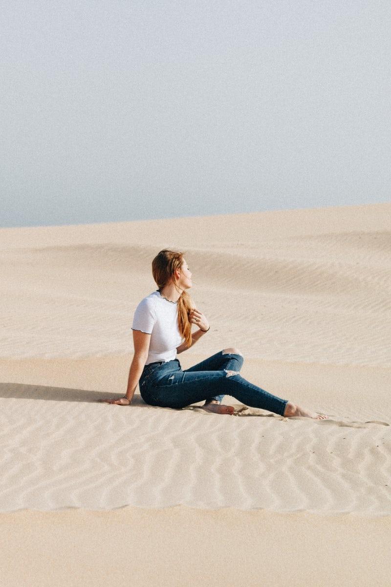 Ragazza seduta nel deserto